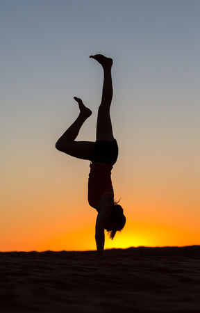 The silhouette of a woman doing a handstand at sunrise, one leg lowered. Stock Photo