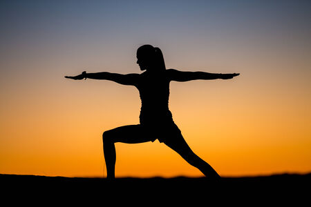 The silhouette of a woman doing the yoga warrior pose at sunrise.