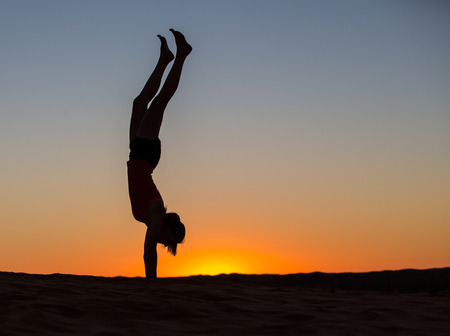 The silhouette of a woman doing a handstand at sunrise. Stock Photo