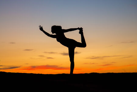 The silhouette of a woman doing the yoga dancer