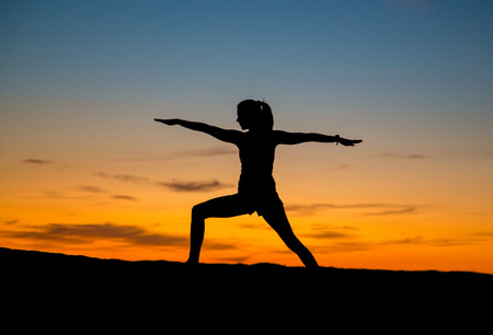 Silhouette of a woman doing yoga with sunrise. Doing the warrior pose.