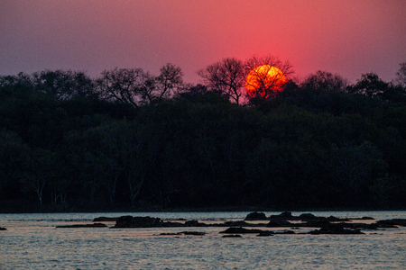 The sun setting over the Zambezi river which splits the two countries, Zambia and Zimbabwe and flows in the direction of the Victoria Falls.