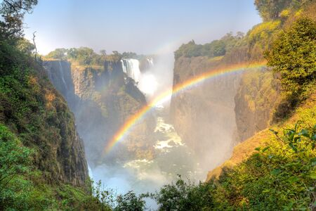 The main falls at Victoria Falls with a rainbow in front.