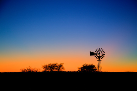 A typical farm setting in the morning with a windpump and the sun about to rise in the background. Slight movement in the blades of the windpump from the wind blowing it on. Stock Photo