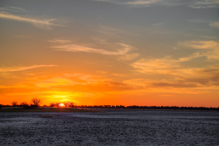 A typical African sunset in Botswana, in this case over a dry pan with rich deep colours.