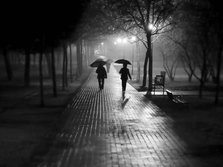 walking in the rain: people walking under rain and fog Stock Photo