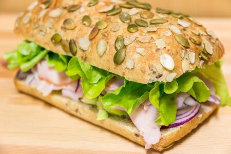 sanwich: Close up Sanwich roll with fresh vegetable and ham on a wooden table Stock Photo