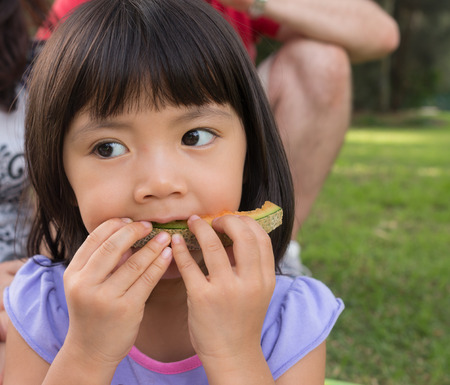 Young girl sitting outside in the park enjoy eating melon Stok Fotoğraf