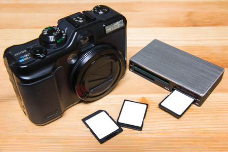 usb card reader with 3 cards and camera on wooden table ready to use