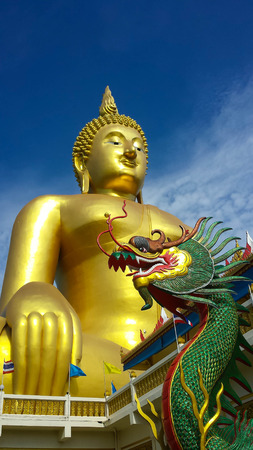 Big Golden Buddha and green dragon statue against blue sky in Thailand temple