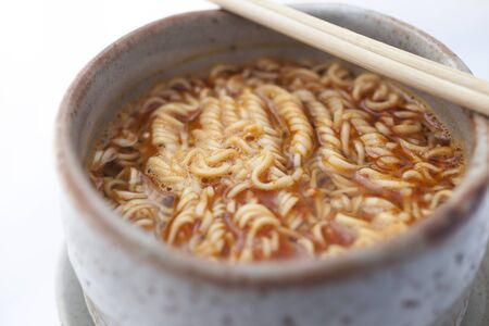 Hot and Spicy instant noodle in clay bowl on white background.