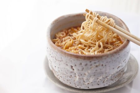 Closeup Hot and Spicy instant noodle in clay bowl on white background. Reklamní fotografie