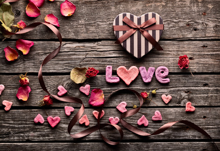 flower boxes: Word Love with heart shaped Valentines Day gift box on old vintage wooden plates. Sweet holiday background with rose petals, small hearts, curved ribbon. Stock Photo