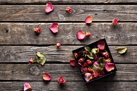 open gift: Many rose petals inside open gift box and scattered on old vintage wooden plates. Sweet holiday background with rose petals. Stock Photo