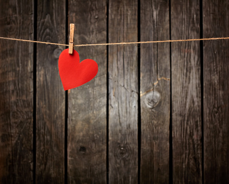 Red paper heart hanging on the clothesline. On old wood background.