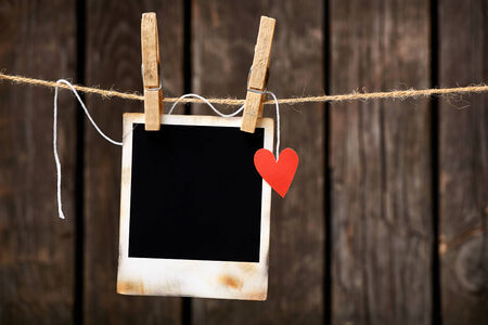 Blank instant photo and small red paper heart hanging on the clothesline. On old wood background. Stock fotó