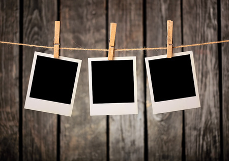 Three blank instant photos hanging on the clothesline. Stock fotó
