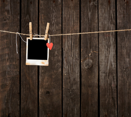 Blank instant photo and small red paper heart hanging on the clothesline. On old wood background. 스톡 콘텐츠