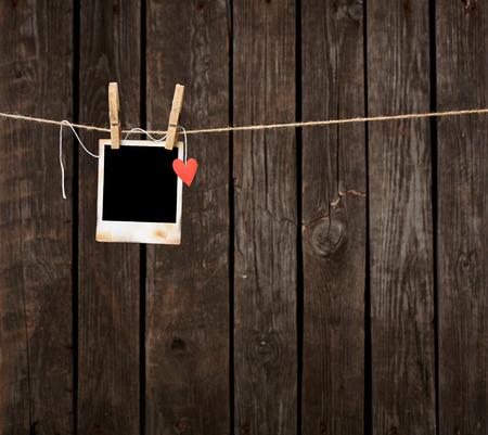 Prázdné instantní fotografie a malé červené papírové srdce visí na šňůře. Na staré dřevěné pozadí.