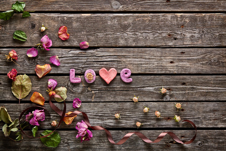 Sweet holiday background with word Love rose petals, small hearts, curved ribbon on old wood. 스톡 콘텐츠