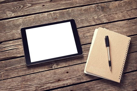 Tablet and notepad on desktop. Clipping path included.