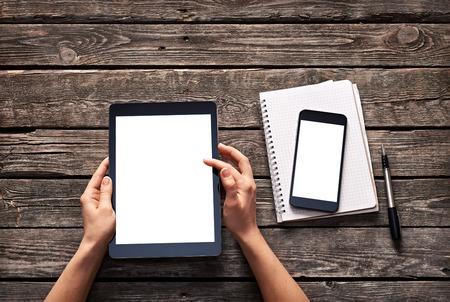 Mujer desplazarse por la pantalla de la tableta digital. Y smartphone es en la libreta. Caminos de recortes incluidos.