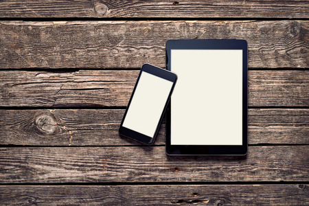 blank tablet: Black Apple devices - Iphone 6 plus and Ipad Air on old wood desktop. Clipping paths included.