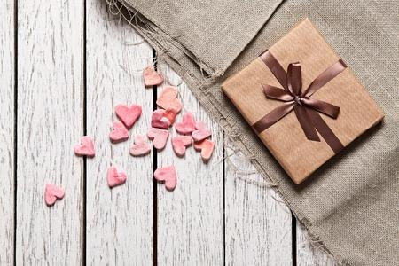 table wood: Geschenkdoos met hoop van kleine harten op witte houten tafel. Stockfoto