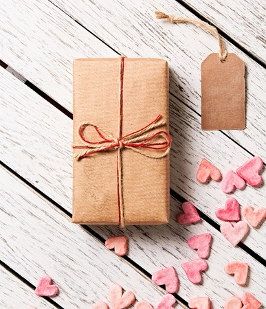 wood box: Gift box with blank gift tag and heap of small hearts on white wooden background.