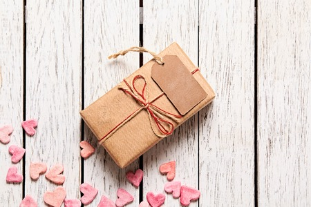 st  valentines day: Gift box with blank gift tag and heap of small hearts on white wooden background.