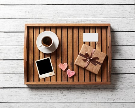 git: Photo frame and hearts and gift box with cup of coffee on wood.