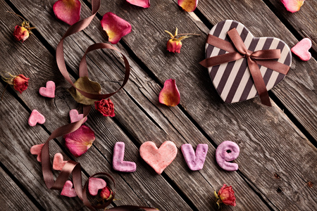 love shape: Word Love with heart shaped gift box on vintage wood table. Stock Photo
