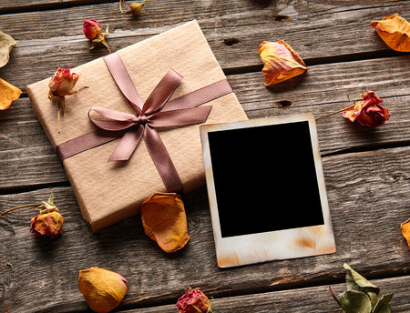 Blank photo frame with gift box, petals and rose flowers on old wooden background. Banque d'images