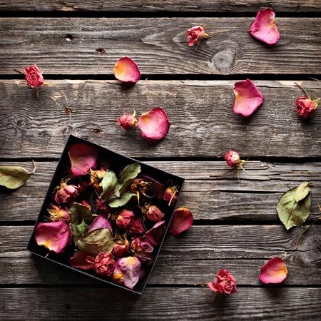 flores secas: Pétalos de rosa en el interior de la caja de regalo abierta y dispersa en placas de madera de época antiguos. Fondo de vacaciones dulce con pétalos de rosa. Foto de archivo
