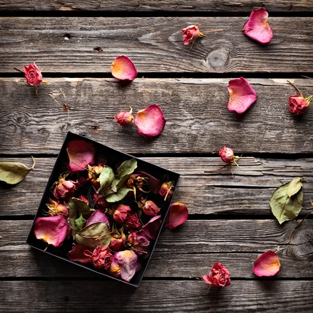 dried flowers: Rose petals inside open gift box and scattered on old vintage wooden plates. Sweet holiday background with rose petals.