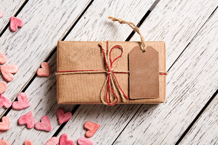 message card: Vintage gift box with blank gift tag and heap of small hearts on white wooden background.
