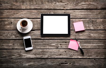 デジタル タブレット コンピューター付箋紙と古い木の机にコーヒーのカップ。単純なワークスペースや web サーフィンでのコーヒー ブレーク。