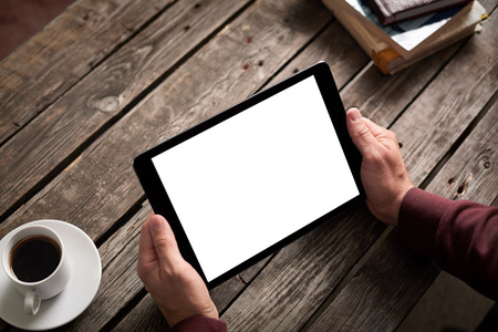 Digital tablet computer with isolated screen in male hands over cafe background - table, smart phone, cup of coffee...