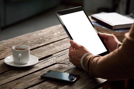 Tablet-computer met geïsoleerde scherm in mannelijke handen over cafe achtergrond - tafel, smart phone, een kop koffie ...
