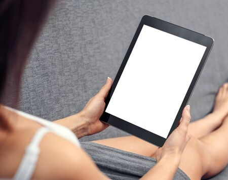 using tablet: Woman using tablet computer while sitting on a cosy sofa. View from above. Clipping path included. Stock Photo