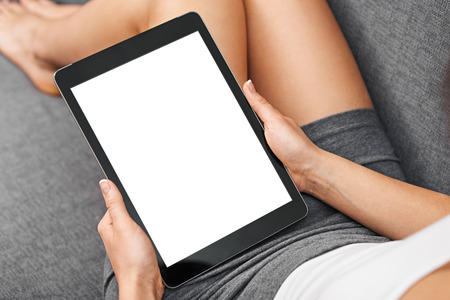 Woman using tablet computer while sitting on a cosy sofa. View from above. Clipping path included. 스톡 콘텐츠