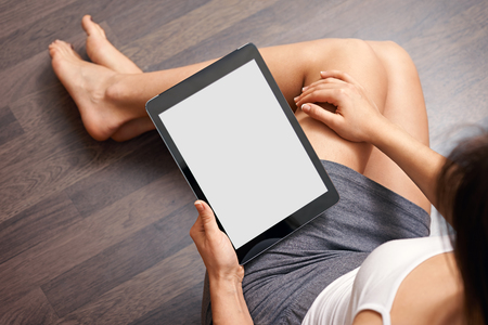 tablet: Woman using tablet computer while sitting on a wooden floor. View from above. Clipping path included. Stock Photo