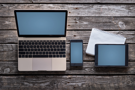 laptops: Responsive mock-up of laptop, digital tablet and smartphone, top view on a desktop. Clipping paths for all screens are included. Stock Photo