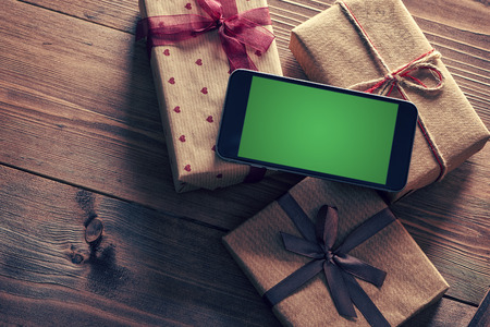 Black smartphone on a heap of gift boxes. Clipping path included. Banque d'images