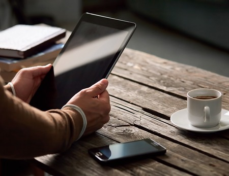 tablet: Tablet computer with isolated screen in male hands over cafe background - table, smart phone, cup of coffee... Stock Photo