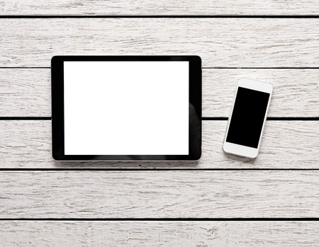 computer screens: Digital tablet computer and white smart phone with isolated screens on white wooden desk. Stock Photo