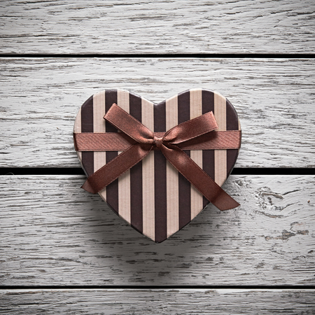 love shape: Heart shaped Valentines Day gift box on white wood. Holiday background.
