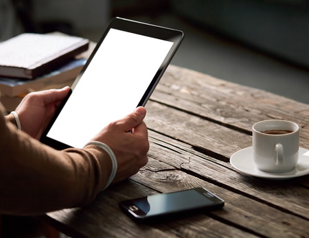 Tablet computer with isolated screen in male hands over cafe background - table, smart phone, cup of coffee... Banque d'images