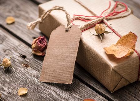 Cadeau tag met cadeau doos op een vintage houten achtergrond. Detailopname Stockfoto