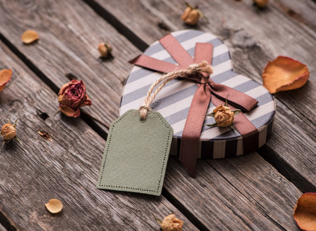 valentine card: Gift tag with heart shaped gift box on a vintage wooden backgrou